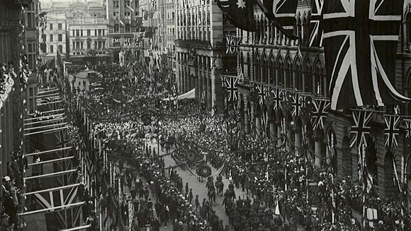 Photograph showing the Royal procession passing along Martin Place towards the Commonwealth Bank.  The foreground shows the procession turning into Pitt Street.