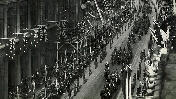 Photograph showing the procession passing along George Street.