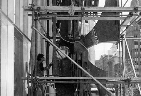 Margel Hinder works on her sculpture outside the Reserve Bank of Australia, 27 October 1964. In September 1961, the Governor of the Reserve Bank, Dr H.C.Coombs, announced an Australia-wide competition for artists and sculptors to design a freestanding sculpture, a mural wall design for the entrance foyer and a formal garden. The American–born artist Margel Hinder was awarded the commission for the sculpture, and her copper and steel artwork is a significant example of Australian modernist abstraction.