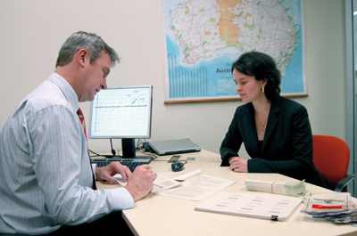 Photograph: Staff in Note Issue Department, Martin Bowerman and Jodie Worby, are shown preparing work in advance of a visit to approved cash centres to select note samples under the Note Quality Reward Scheme (NQRS). The Reserve Bank established the NQRS with commercial banks in September 2006 as a means of improving the quality of notes in circulation.