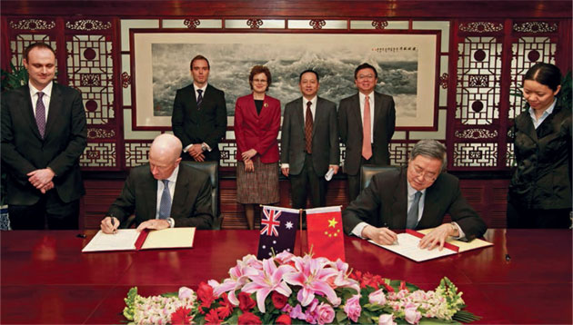 Governor Glenn Stevens and PBC Governor Zhou Xiaochuan signing the swap agreement at a ceremony in Beijing, in the presence of the RBA's representative in China, Ivan Roberts (far left) and the PBC's Lü Tingting (far right); behind them are the RBA's Mark Hack, Frances Adamson (Australia's Ambassador to China), Song Xiangyan, PBC Deputy Director-General, International Department, and Li Bo, PBC Director-General, Monetary Policy Department II