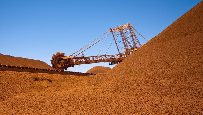 Heavy mining equipment sits among large piles of red earth
