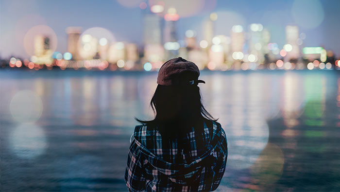 A young woman looks out across the water towards an illuminated city skyline.