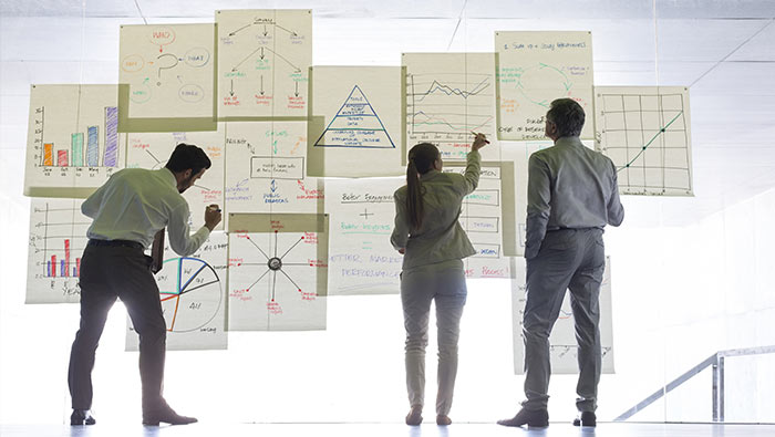 Three employees work on large charts stuck to a transparent wall