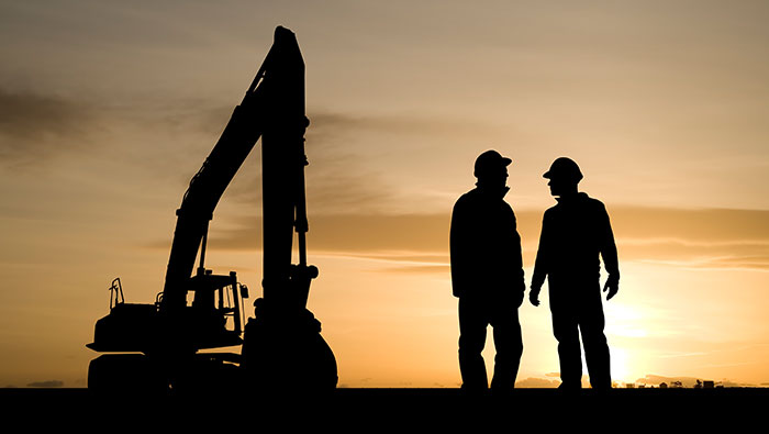 The outlines of two miners and an excavator against a sun setting.