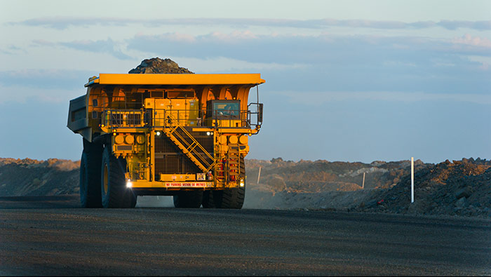 A large loaded mining truck drives through a featureless landscape.