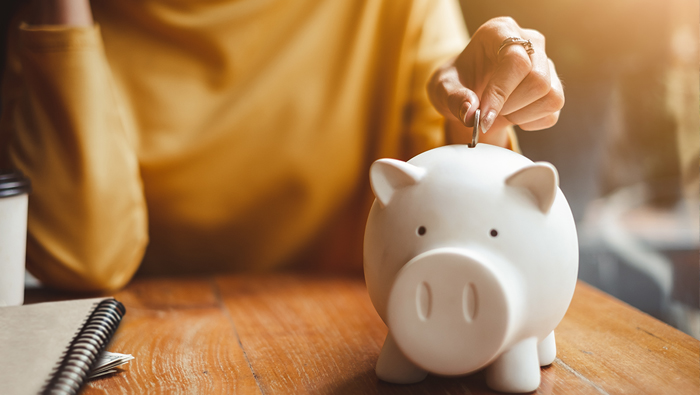 The hand of a woman inserts a coin into a piggy bank.