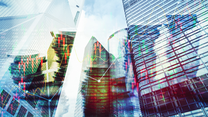 Outlines of skyscrapers and images of charts mirror on glass facades.